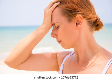 Headache woman on sunny beach. Woman with sunstroke. Hot sun danger. Health problem on holiday. Medicine on vacation. Dangerous sun. Beach life. Sunstroke on sunny beach. Healthcare in tropics