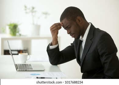 Headache at work concept, stressed african-american businessman feels strong sudden migraine working on laptop at workplace, frustrated dizzy black man in suit touching head tired of chronic fatigue