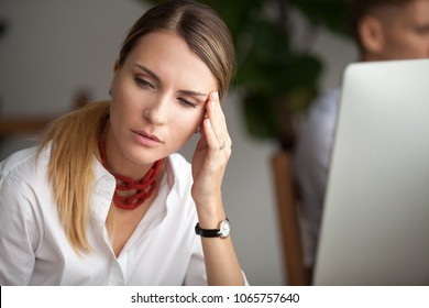 Headache at work concept, stressed businesswoman feeling strong migraine working on computer at workplace, frustrated dizzy woman touching temples tired of aching head or chronic fatigue in office