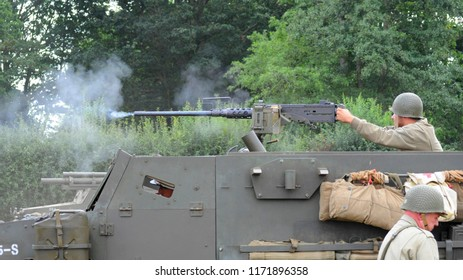 Headcorn Aerodrome, Kent / UK - 08/19/2018: Re-enactor in WWII US army uniform firing M2 Browning .50 caliber machine gun from M3 half-track at the 2018 Combined Ops Military & Air Show.