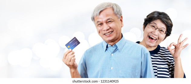 Header of happy asian cheerful senior couple, retirees or older parents smiling and showing credit card with satisfaction in elderly consumer shopping experience concept on isolated white background.