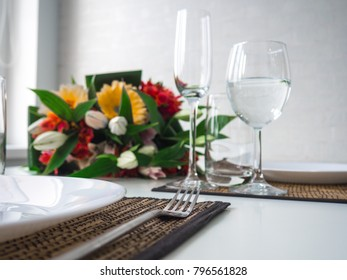 Header hero image for website table setting, a bouquet of lilies and gerberas, forks, plates, a cozy dinner