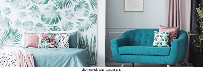 Header of an open space living room and bedroom interior with floral cushions and leaves pattern wallpaper