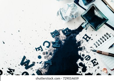 Header with spilled ink, crumpled paper, scattered letters, papers and notepads on a white wooden background. Creative writing concept. Flat lay with copy space. High key still life with an inkwell.