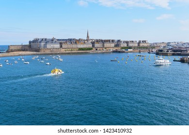 Heading out to see from the post of Saint Malo, France. A small boat travels across the harbour.