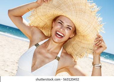 Heading to white sand blue sea paradise. Smiling woman in white swimsuit playing with big straw hat at sandy beach on a sunny day