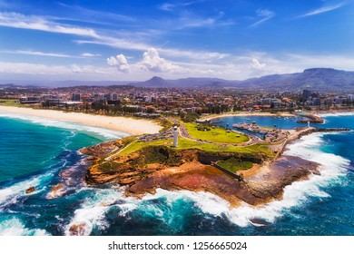 Headland of Wollongong city on Pacific coast of Australia with two white lighthouses guarding and protecting town harbour and marina in aerial view from open sea.