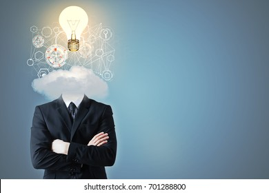 Headless businessman with cloud, business hologram and glowing lamp instead of head on blue background. Media concept
