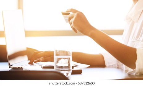 Headless crop of a black female busy using a laptop computer to make online payments using her credit card.