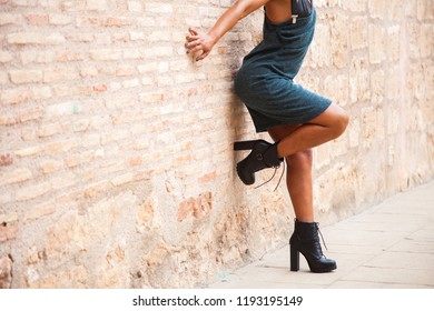 Headless female model with summer clothing supported on a stone wall