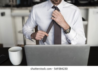 Headless man at desk adjusting his tie in front of laptop with coffee