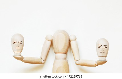 Headless man holds two heads with different emotions. Abstract image with a wooden puppet