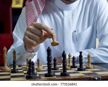 A headless shot of an Arab man playing chess at his desk, wearing Saudi Arabian thob #1
