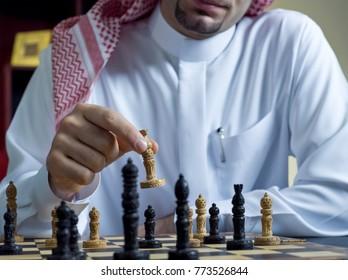 A headless shot of an Arab man playing chess at his desk, wearing Saudi Arabian thob #2