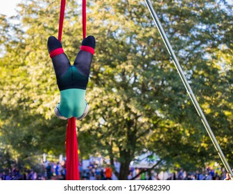 A headless woman is hanging upside down on a red ribbon
