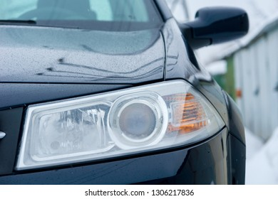 Headlight of the car in the background of the garage in the winter