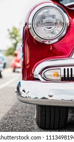 The headlight and chromed front end of an early fifties classic American car.