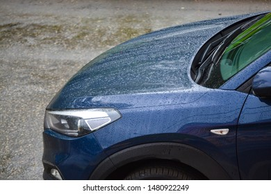 Headlight of a dark car and hood covered with drops of water after rain, close-up.