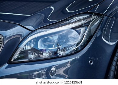 Headlight detail of blue car. Close up of modern sedan headlamp. Front view shot from side of vehicle. Illustration of lens and reflector design in the front of automibile. Car headlight background.