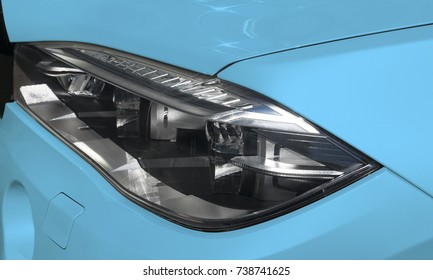 Headlight of a modern blue sport car. The front lights of the car. Modern Car exterior details