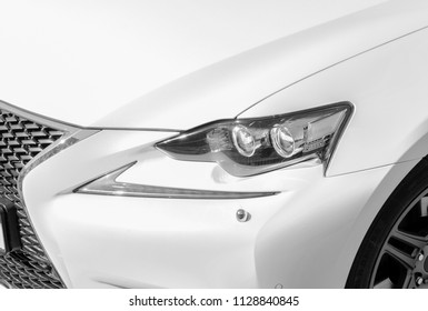 Headlight of a modern white sport car. The front lights of the car. Modern Car exterior details. Car detailing