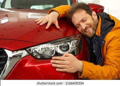 Headlight of new red car and handsome man close to. Happy man smiling and holding hands on top of car and hugging it. Concept of purchase of automobile in car dealership.