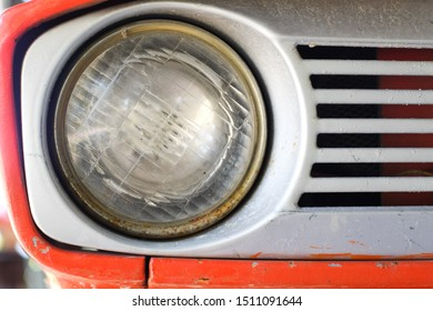 Headlight of the old orange tractor close-up.