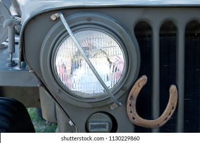 A headlight of old used military vehicle with horseshoe