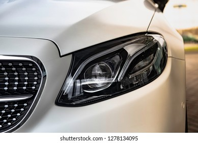 headlight and radiator grille of a beautiful matte white car with sun rays
