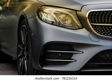 headlight and radiator grille of a beautiful matte gray car with yellow tint