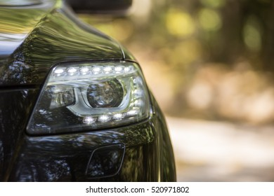 headlights of black car. Outdoors.