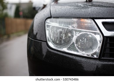 headlights of black car. Outdoors. With rain drops.