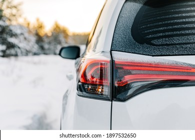 The headlights of a car. Close-up of the rear light of a car on a winter road.
