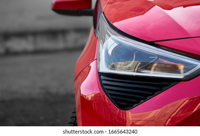 Headlights and hood of sport red car with silver stars. Car detail