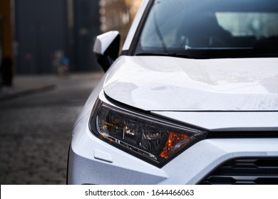 Headlights and hood of sport white car with silver stars