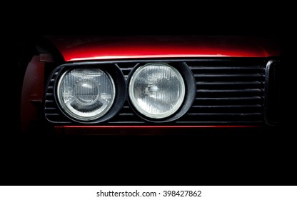 Headlights of the old red car close-up photo.