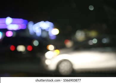 Headlights reflecting off of a lightly   colored car make it  the focal point of this softly focused night time city street shot.
