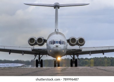 A head-on shot of a large multi-engine military aircraft powering down the runway.