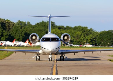 Head-on view of a business jet at an airport taxiing after landing