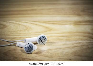 Headphone or earphone  on wooden background.