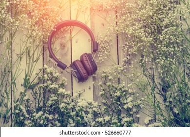 headphone with frame of beautiful flower on wooden background music therapy concept