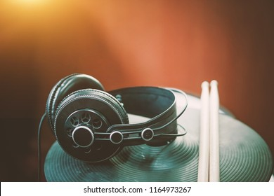 headphone on drumstick or electronic drum blur background by vintage tone.