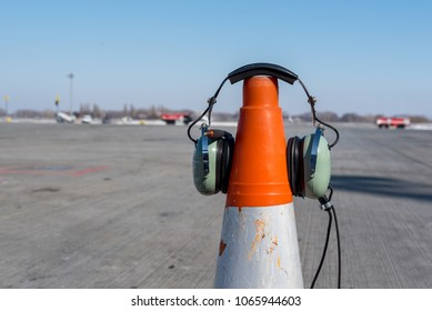 Headphones of aircraft technician, who conducts preflight preparation of the aircraft, are put on an orange cone. Technician checking engine of civil airliner concept