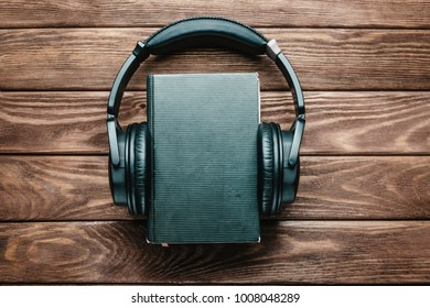 Headphones around a paper book on a wooden background, space for text on the cover of book. Concept of audiobook.