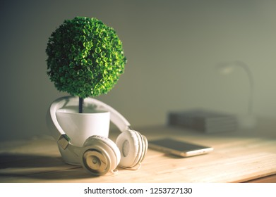 headphones and artificial tree with morning light relax background music concept.