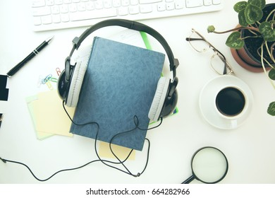 Headphones and  book with keyboard and stationary on the  white table