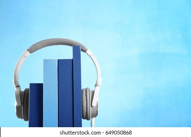 Headphones and books on color background. Concept of audiobook