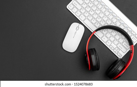 Headphones with computer keyboard and computer mouse on black. Top view. Space for text.