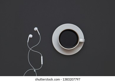 Headphones and a Cup of coffee on a black background. Musical concept. Top view with copy space.