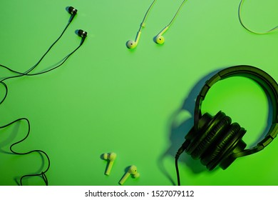 Headphones of different types flat lay on green color background, copy space. Black in ear headphones, wireless and foldable over ear headphones closeup with cable, music concept, top view.